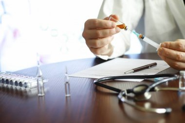A man signs a medical document. Medical equipment on the table.