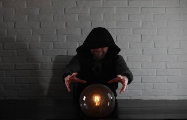 A man with a fortune teller ball at the table