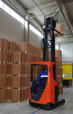 Warehouse worker driving forklift with palette.