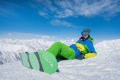 dívka leží na sněhu s snowboardové prkno. Zima. Mo