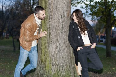 Young couple in love are chasing around a tree