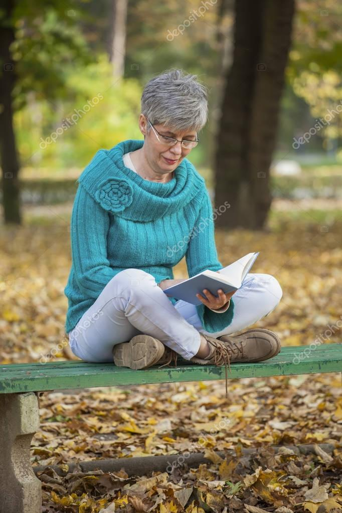 Older woman in the park reading a book