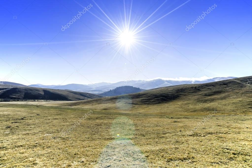 Landscape view of mountain pastures and the sun at its zenith