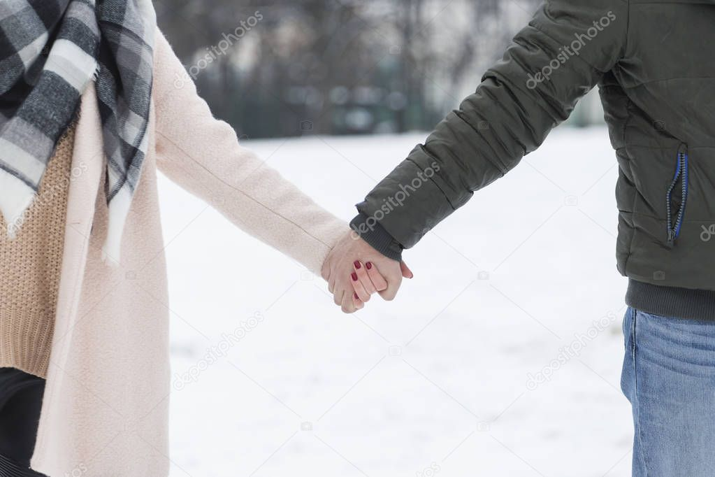Couple holding hands walking on the snow