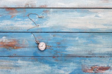 Old pocket watch on a wooden board