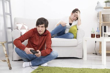 Girl is bored and angry while her boyfriend playing video game