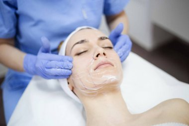 woman at spa salon applying facial mask