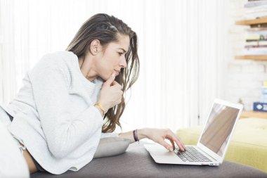 Morning scene. Beautiful woman using laptop at home