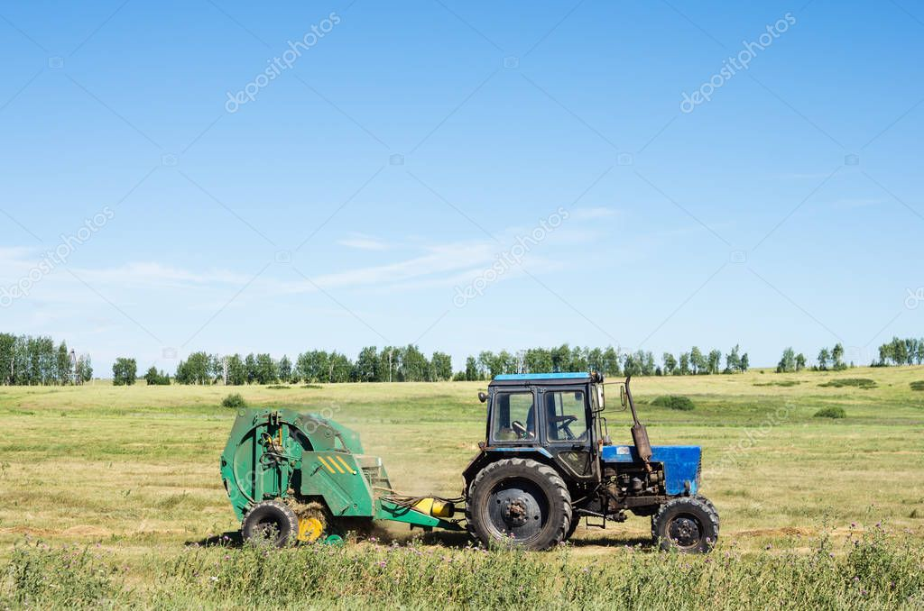 Tractor with trailed stacker, removes from the field the hay