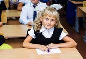 Fotografie Erstklässler Mädchen sitzen an einem Schreibtisch in der ersten Lektion am 1. September