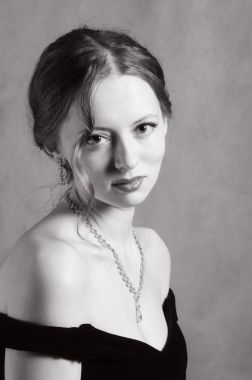 Beautiful girl in evening dress with neckline. Black and white portrait in retro style
