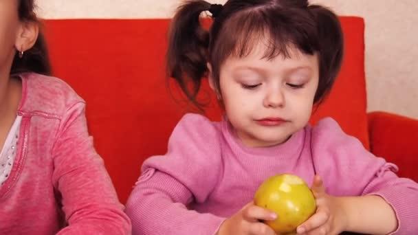 Děti jíst jablka. Dvě sestry jíst žluté jablka zatímco sedí na oranžový gauč