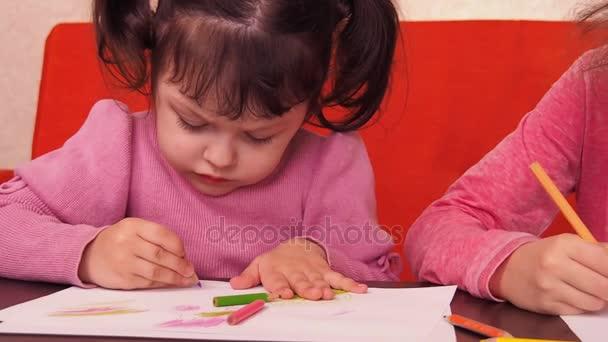 Děti namalovat tužky. Dvě malé holčičky nakreslit na papír s pastelkami