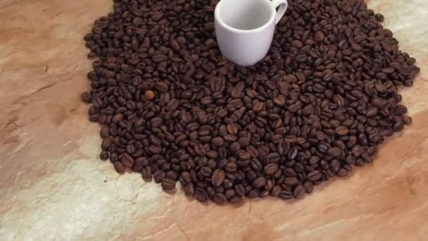 White cup of coffee beans. A small white cup on a coffee cup. In the kitchen on the table.