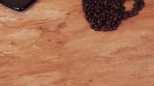 A cup of coffee beans and a mobile phone. On the kitchen marble table the sign of a cup of coffee beans and mobile.