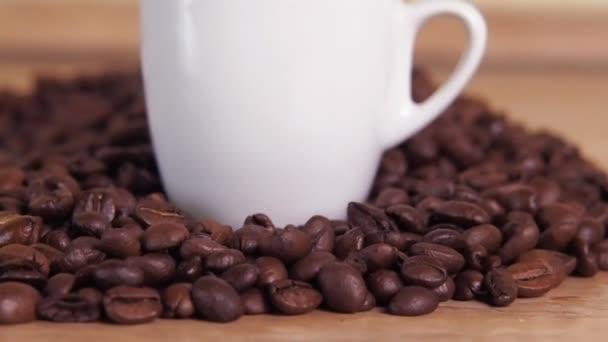 Bílý hrnek a žlutý květ na kávová zrna. Malý bílý hrnek v kávová zrna. Žlutý Tulipán na kávová zrna
