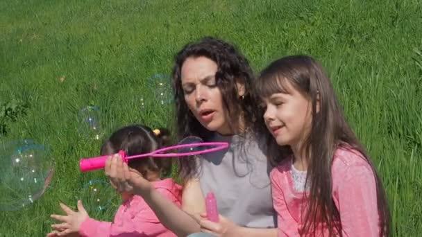 Děti s mámou zahrávají s mýdlovými bublinami. Šťastná rodina na přírodu v létě. Dívka s dětmi v parku na slunečný den hraje s bublinkami