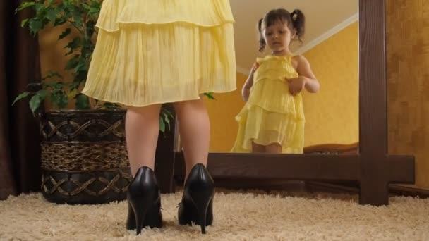 239ed60df Una niña en sus zapatos de las madres por el espejo. Un niño hermoso en un  vestido amarillo se ...