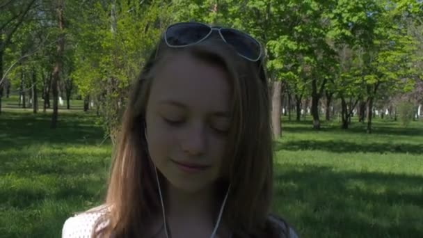 Teen girl in headphones. A girl in sunglasses and with a phone listening to music. A sunny day in the park.