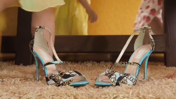 Little girls play with their mother's shoes. Sisters measure shoes on heels. Two children's feet wear shoes.– stock footage
