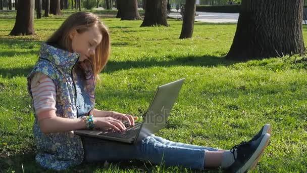 Kind am Laptop in der Natur arbeiten. Ein junges Mädchen mit Sonnenbrille sitzt auf dem Rasen im Park. Mädchen im freien Sonnentag mit laptop