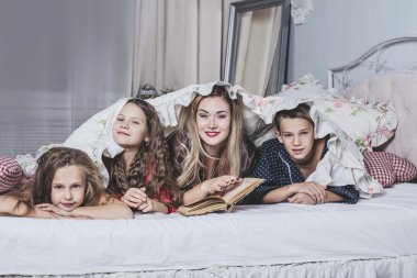 One big happy family. Mom reads a book to their children in bed.