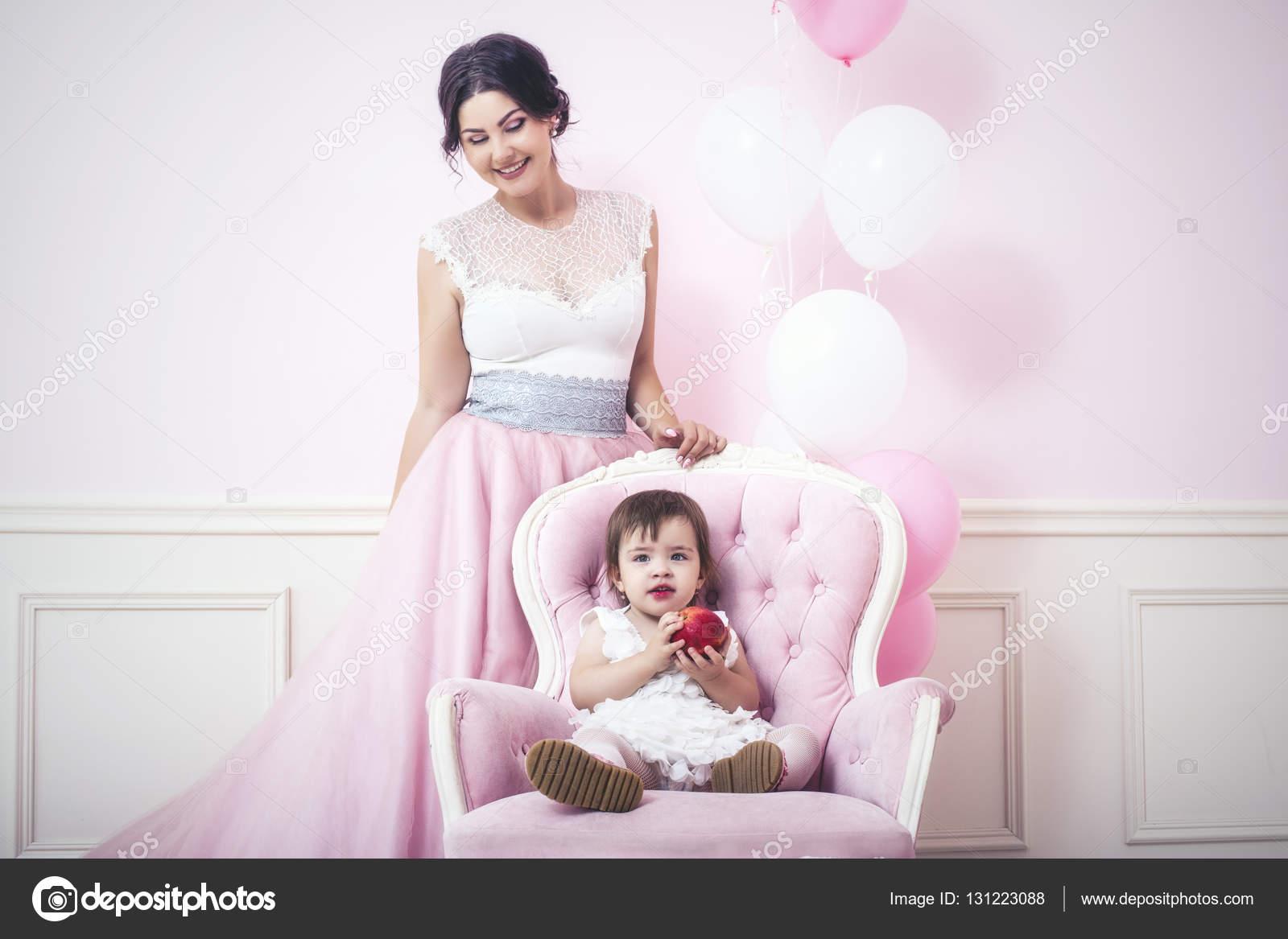 Madre e hija un hermoso y feliz rosa interior con vin — Foto de ...