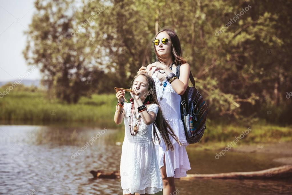 Beautiful and happy young mother and little daughter on nature b
