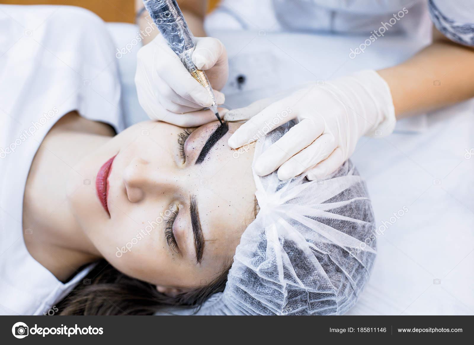 Beautician Female Applies Permanent Makeup On Eyebrows Tattoo E