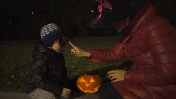 Mother and her son watching jack olantern on halloween night