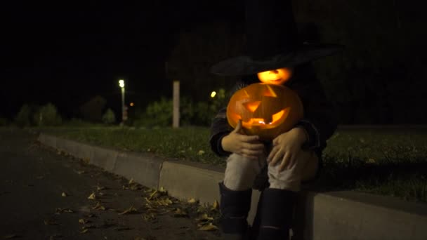 Little boy sitting alone with jack olantern at night parking