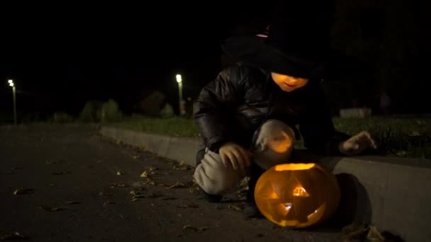 Little boy putting lights in jack olantern
