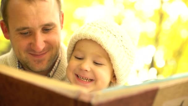 Father and his son having fun in study interesting book in yellow autumn forest