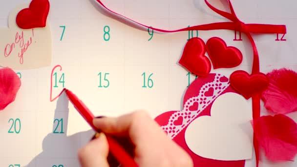 Ženská ruka označení 14.února na stránce kalendáře