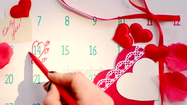 Woman hand drawing hearts on calendar page on Valentines day