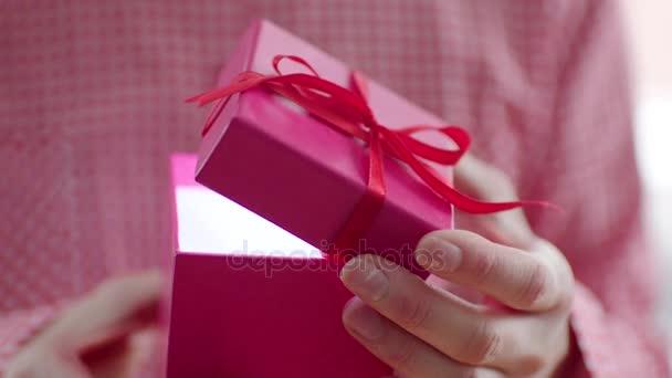 Nő nyitó ünnep ajándék piros szalaggal és fény belül