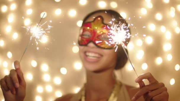Vidám, fiatal nő a maszk, a csillagszórók karácsony estéjén