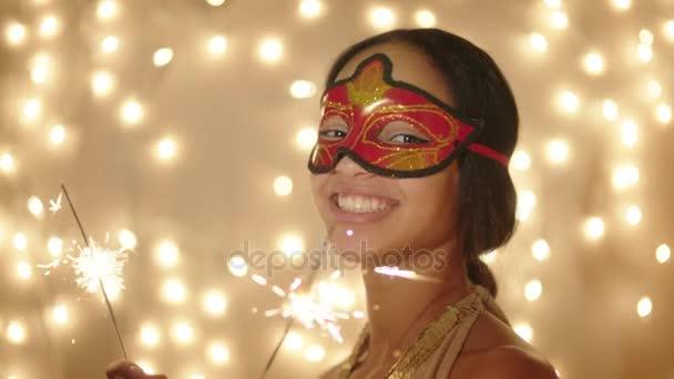 Krásná mladá žena nosí karneval maska s bengálskou červení světla ve svých rukou