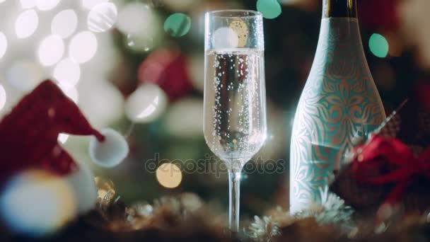 Sklenice plná šampaňského a láhev šampaňského na silvestrovský večer
