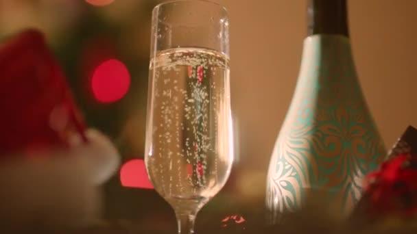 Sklo plné šampaňské a láhev šampaňského na nový let. Zdobené vánoční strom rozostřený