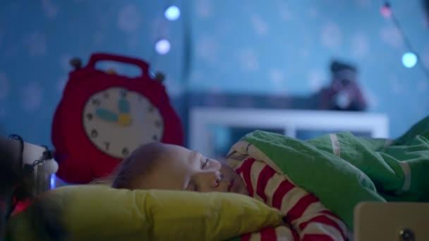 Santa Claus přináší dárky na Štědrý večer zatím chlapečka spí ve své postýlce