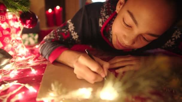 Dospívající dívka přepisování vánoční dopis Ježíškovi na Štědrý den