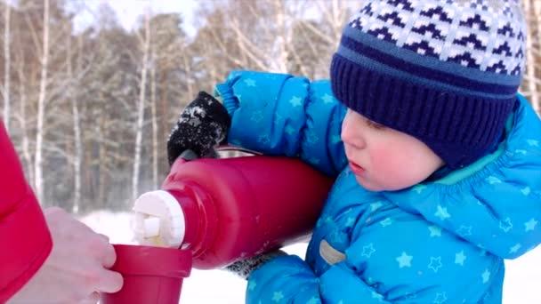 Nahaufnahme eines kleinen Jungen, der bei einem Winterspaziergang heißen Tee aus der Thermosflasche in die Tasse gießt