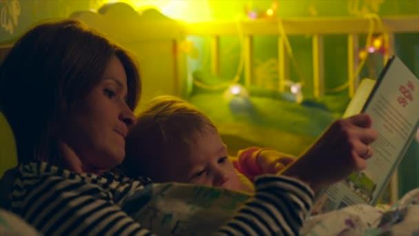 Anya olvasó könyv éjszaka kis fiát, a kiságy