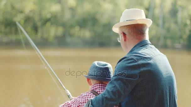 Der kleine Junge schwingt selbst die Angelrute. Sein Opa hilft ihm