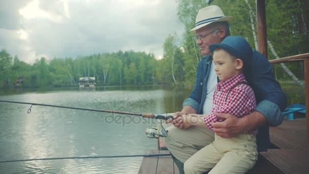 hübscher Junge und sein Opa angeln am See