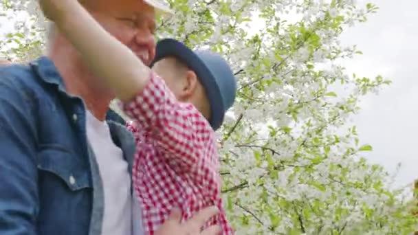 Kleiner Junge und Opa im blühenden Garten