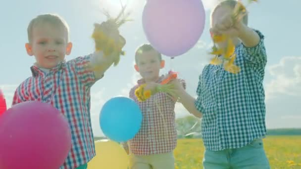 Three little boys smiling with colour balloons and flowers