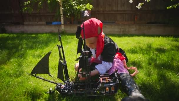 Malý chlapec na sobě kostým pirát hraje hračka lodi pirátů z Karibiku na trávníku na Halloween