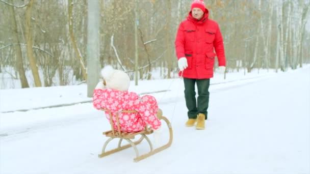 Šťastný chlapec na saních v zimě parku s dědečkem